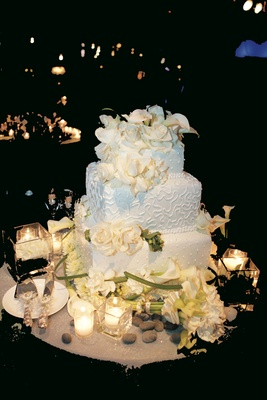 Three layer cake surrounded by flowers and candles