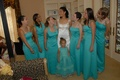 Bride in a Reem Acra gown with bridesmaids in long teal dresses