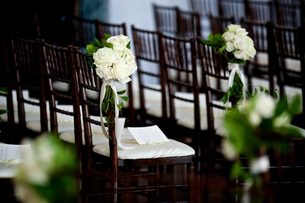 Wedding ceremony with dark chiavari chairs, white cushions, white roses, greenery, white ribbons