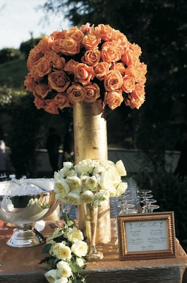 Wedding cocktail table decorated with tall arrangement of roses and short arrangement of peonies