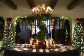 Wedding reception escort card table with holiday Christmas theme and antler garland arrangement