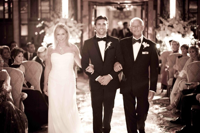 Unsaturated photo of groom walking down aisle with mom and dad