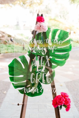 wedding welcome sign green tropical jungle leaves bright pink flowers lucite acrylic sign white