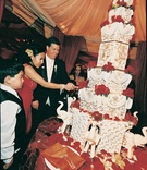Bride and groom cut seven tier white, gold, and red cake