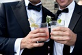 Groomsmen male wedding guest cheers holding cocktails in tumbler glasses limes custom stir sticks