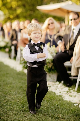 Cute blond ring bearer on grass aisle white flower petals vest boutonniere and bow tie