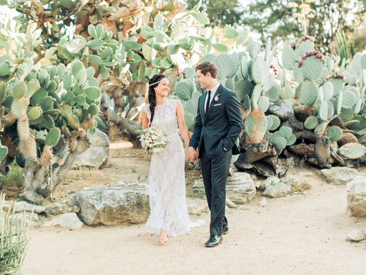boho-chic bride and groom walk hand-in-hand, bride with jeweled headband, desert wedding