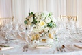small, low centerpiece with white flowers and eucalyptus leaves, surrounded by gold votive candles