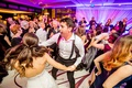 bride and groom dancing on dance floor with rose gold monogram purple pink lighting live band
