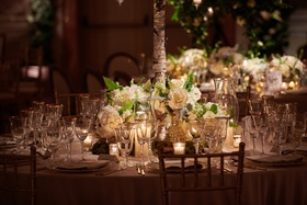 ivory flowers at base of birch branch holding up centerpiece