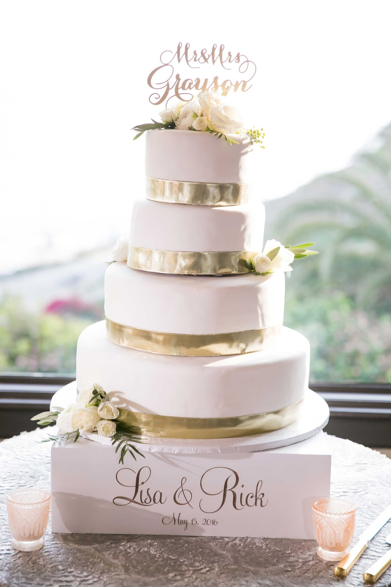wedding cake from gelson's, four tiered, gold ribbon at base of each layer, white frosting