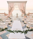 ca' d'van wedding ceremony on porch overlooking ocean, chiavari chairs in half circle, blush chuppah