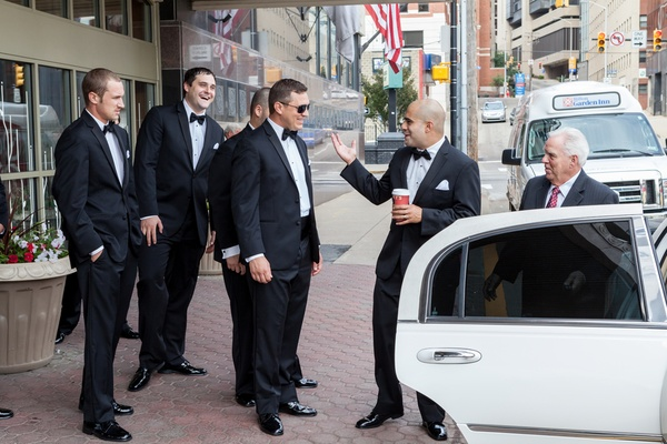 Groom with friends in tuxedos getting into white sedan