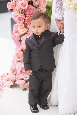 Adorable ring bearer in black suit and bow tie with patent leather shoes holding mom's hand bride