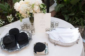 Silver platter of yarmulke black and white handkerchief at outdoor Jewish wedding ceremony