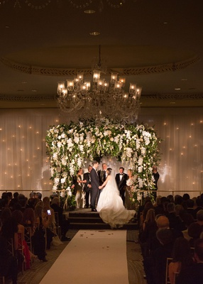 wedding ceremony ballroom chuppah twinkle lights behind drapery white orchids blush flowers