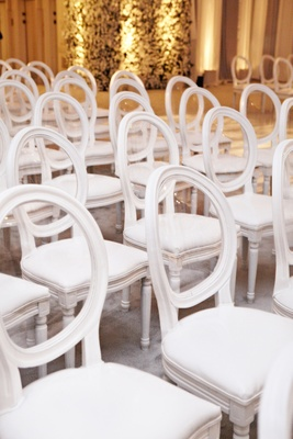 White ceremony chairs with clear round backs and plush cushions