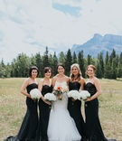 bride in watters mermaid wedding dress, bridesmaids in black gowns with sequin bodices