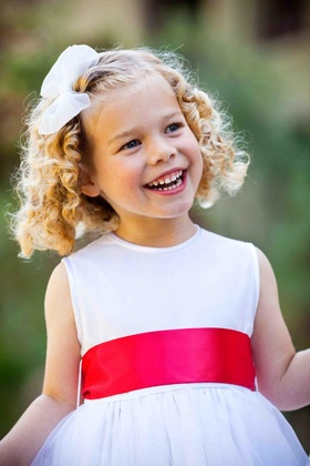 White flower girl dress with pink-orange sash