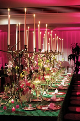 table covered with green tablecloth and candelabras of twisted branches