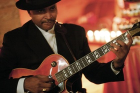 African American man playing guitar in black hat
