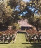 Winery wedding, wood chairs with garlands of greenery on backs winery vineyard outdoor wedding