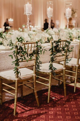 wedding reception gold chair with greenery and flowers white cushions head table ballroom carpet