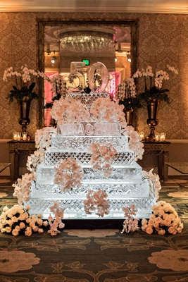 wedding anniversary party ice sculpture in shape of cake with fresh flower decorations and 50 cake t