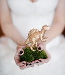 Bride holding moss pillow with golden dinosaur figurine