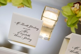 White seating cards with black calligraphy lettering