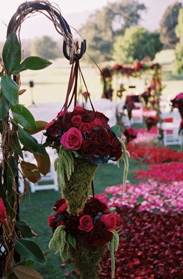 Pink and red flowers hanging from iron hook