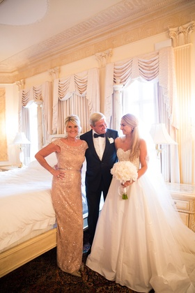 Bride in strapless Reem Acra wedding dress with bouquet in bridal suite with mom in sparkly dress
