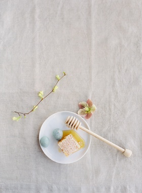 honey dipper with honeycomb and robin eggs on small white plate