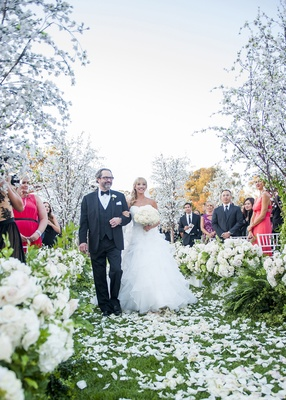 bride in full ball gown walking down the aisle with her dad, outdoor wedding with flower petals