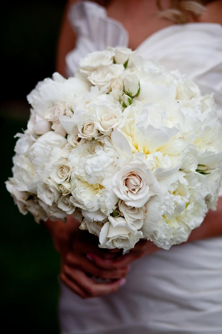 Bride holding white wedding bouquet with peonies and roses