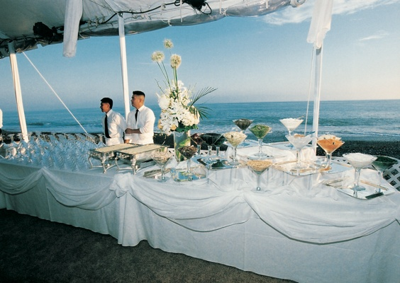 White buffet table in front of ocean with food and drink spread