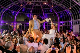 Bride and groom on chairs in crowd at purple wedding reception