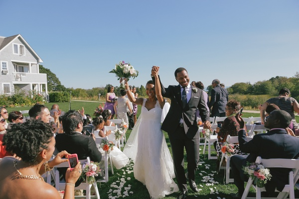 Bride and groom walk up flower petal aisleway at outdoor ceremony