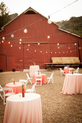 Pink cocktail tables on rustic lawn outside of red barn