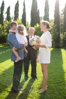 Bride in a short Mod dress with 3/4 sleeves, groom in blue coat, black pants carries daughter