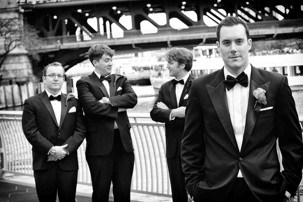 Black and white photo of groom and groomsmen in tuxedos by Chicago River