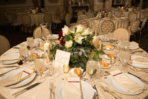 Holiday wedding reception table with evergreen, white amaryllis, red roses, holly, christmas lights