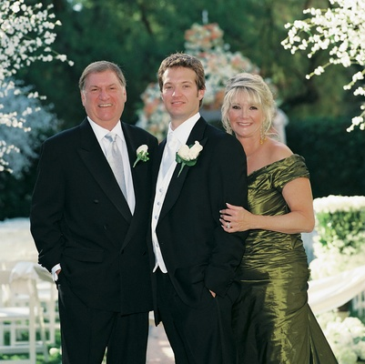 Groom with father of bride and mother of bride in green formal dress