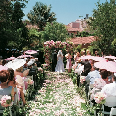 Pink and white rose and hydrangea flowers decorate outdoor ceremony