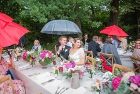 bride and groom at head table with guests rain on wedding day umbrellas for guests