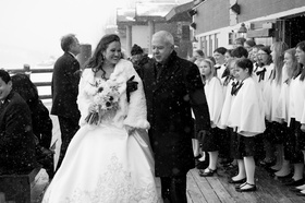 Black and white photo of bride walking with father