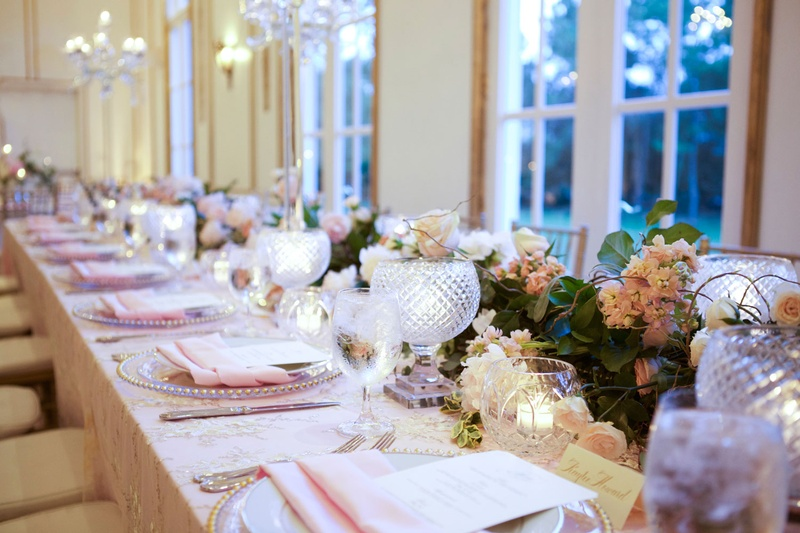View of long table with flower runner, cut-crystal candle votives, pink napkins atop gold charger