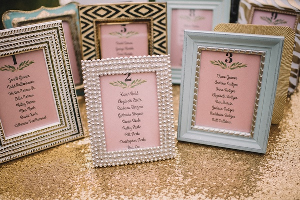 Mismatched frames with pink seating charts for tables