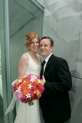 Bride and groom with vibrant orange and pink wedding flowers