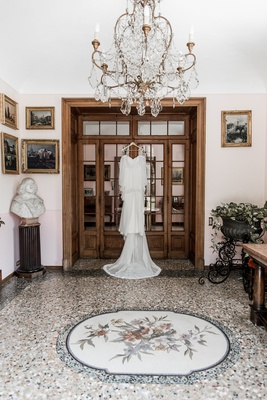 wedding dress hanging up on door frame in italy switzerland villa ornate decor